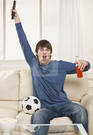 Man Cheering at Game stock photo, A young man is sitting on the couch in his living room and watching a sports game.  He is holding a remote control, a soda, and there is a soccer ball right next to him.  He is looking at the camera.  Vertically framed shot. by Jonathan Ross