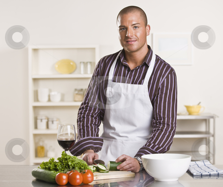 Man Preparing Meal stock photo, A young man is in his kitchen and is chopping vegetables to prepare a meal.  He has a glass of wine and is looking at the camera.  Horizontally framed shot. by Jonathan Ross