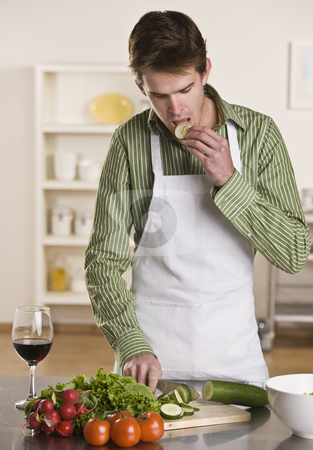 Man Preparing Meal stock photo, A young man is in his kitchen and is chopping vegetables to prepare a meal.  He has a glass of wine and is eating a piece of cucumber.  He is looking away from the camera.  Vertically framed shot. by Jonathan Ross