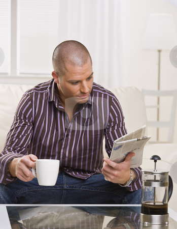 Man Reading Paper - Vertical stock photo, A young, attractive man is sitting at a coffee table, drinking coffee and reading a newspaper.  He is looking away from the camera.  Vertically framed shot. by Jonathan Ross