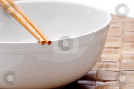 A horizontal image of a pair of chopsticks on a white bowl on a  stock photo, A horizontal image of a pair of chopsticks on a white bowl on a weaved placemat by Vince Clements