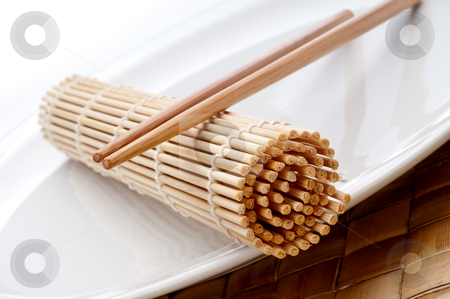 A tilted horizontal macro of a pair of chopsticks and a sushi ro stock photo, A tilted horizontal macro of a pair of chopsticks and a sushi rolling mat on a white plate by Vince Clements