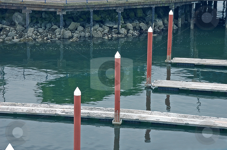 Diagonal Row of Pillars stock photo, This boat marina scene shows a diagonal pattern of pillars along side docking areas. by Valerie Garner
