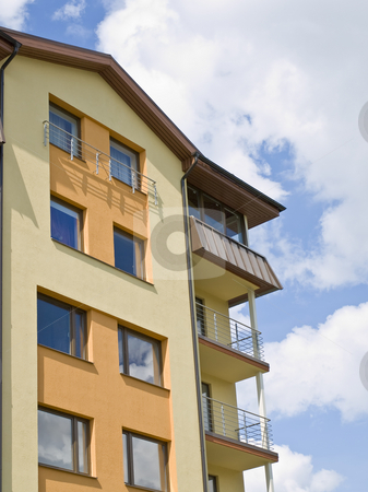 Mansion stock photo, Flat building against the blue sky with clouds by Sergej Razvodovskij
