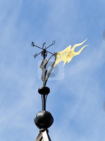 Weather vane  stock photo, Metallic weather vane against the blue sky by Sergej Razvodovskij