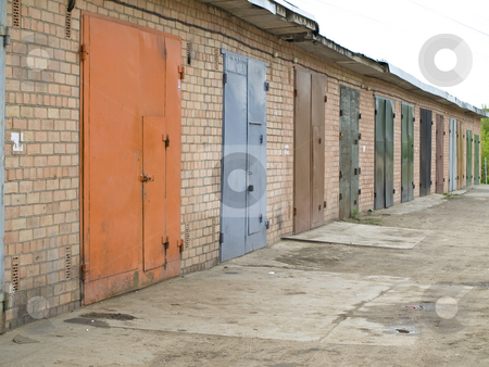 Garage row stock photo, Row of garage with multicolored metalic doors by Sergej Razvodovskij