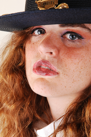 Girl security guard. stock photo, Pretty red haired woman security guard with the big black hat an white blouse on white background. by Horst Petzold