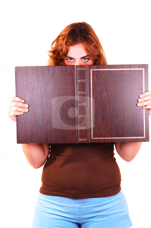 Woman holding book. stock photo, Young woman in brown top and light blue shorts holding a brown book up to her eyes and looking over the edge of the book. by Horst Petzold