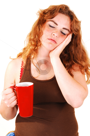 Sleeping girl with coffee. stock photo, An sleeping girl with her hand on the face and holding an big red coffee cap in the her hand. by Horst Petzold