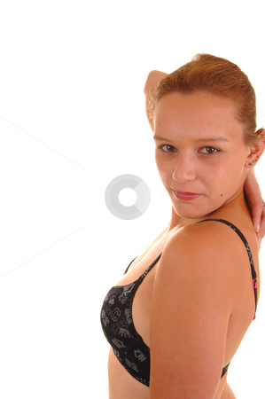 Woman in black bra. stock photo, Young woman shooing her chest with an black bra on her small breasts in close up on white background. by Horst Petzold