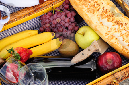 Inside A Picnic Basket stock photo, Closeup of the contents of a picnic backet these include red wine, grapes, red and green apples, kiwi fruit, bannas, strawberries amd a loaf of french bread by Lynn Bendickson