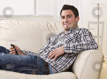 Attractive brunette male sitting on couch. stock photo, Attractive brunette male sitting on couch holding a remote, smiling at the camera. Horizontal. by Jonathan Ross