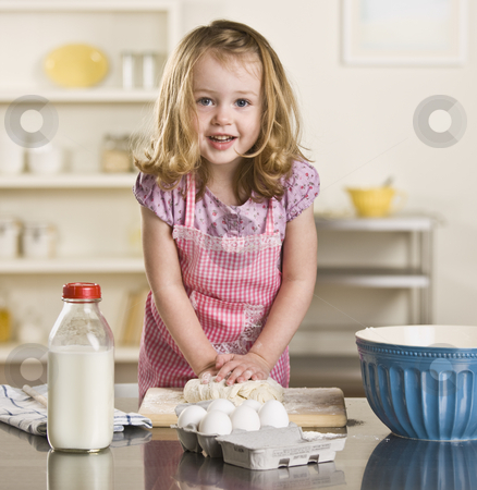Little girl baking stock photo, Cute blond little girl making bread in the kitchen. Milk bottle, bowl and eggs on the counter. Square by Jonathan Ross