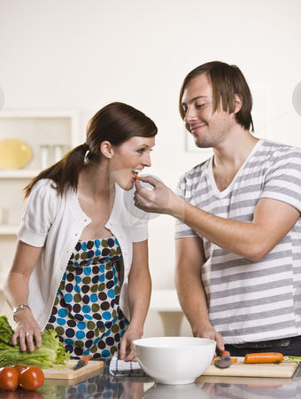 Attractive man feeding woman stock photo, Attractive male feeding attractive female  a piece of carrot. They are in the kitchen and working over the counter. vertical by Jonathan Ross