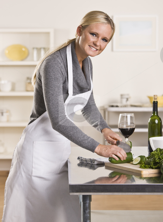 Attractive woman slicing cucumber stock photo, Attractive blond woman slicing cucumber smiling at the camera. Glass of red wine in background. Vertical by Jonathan Ross
