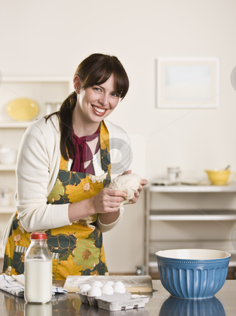Brunette Kneading a Ball of Dough stock photo, Brunette showing bread dough to the camera while smiling and wearing an apron. On the counter is a bowl and milk bottle. by Jonathan Ross