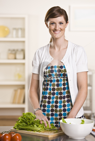 Attractive brunette in kitchen stock photo, Attractive brunette in kitchen making a salad with a polka dot dress and white cardigan short sleeved sweater. vertical by Jonathan Ross