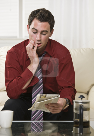 Attractive male reading Newspaper stock photo, Attractive male reading the paper with a concerned and focused look on his face. Drinking coffee, looking at the paper. vertical. by Jonathan Ross