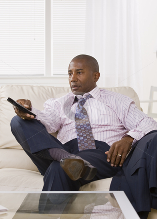 African American male watching TV stock photo, African American male watching TV while sitting on the coach in a shirt and tie. vertical. by Jonathan Ross