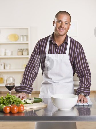 Attractive male chef stock photo, Attractive male chef in the kitchen with vegetables and a glass of wine on the counter. Vertical by Jonathan Ross