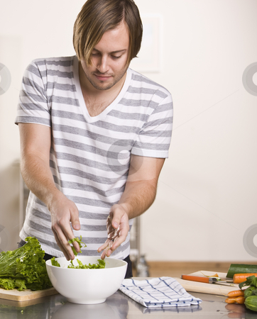 Attractive male making salad stock photo, Attractive long haired male making salad. vertical by Jonathan Ross
