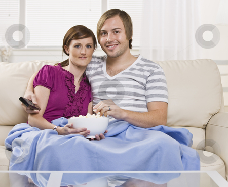 Attractive couple eating popcorn. stock photo, Attractive couple eating popcorn on the coach with blanket and holding a remote. Horizontal. by Jonathan Ross