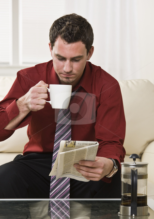 Attractive man drinking coffee stock photo, Attractive man drinking coffee while reading the paper sitting on the coach. vertical by Jonathan Ross