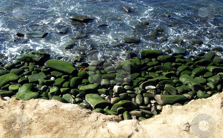 Green mossy rocks along the coast stock photo, View of pacific coast with mossy rock and gentle surf by Jill Reid
