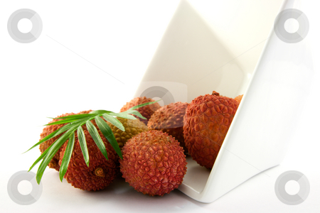 Lychee Spilling out of a Dish with Leaf stock photo, Lychee and green leaf spilling out a dish with clipping on a white background by Keith Wilson
