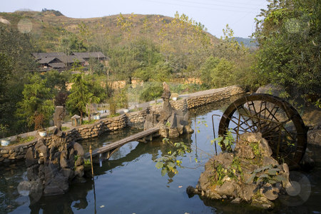 Rural Village Guizhou China stock photo, Pond and Garden with Wheel in front of village in countryside, Guizhou, China by William Perry