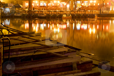 Wooden Boats Houhai Lake Beijing China at Night stock photo, Wooden Boats on Houhai Lake with Lights of Bars and Restaurants in background, Beijing, China.  Hohai is the old swimming hole in the City and is now surrounded by bars and restaurants and is one of the well-known night districts in Beijing. by William Perry