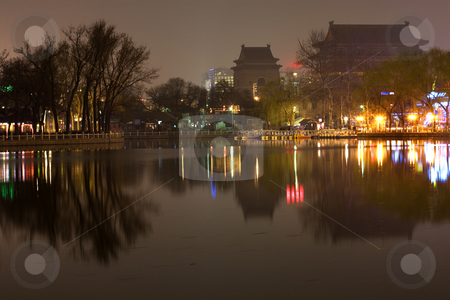 Houhai Lake at Night With Drum and Bell Tower Beijing, China Tra stock photo, Houhai Lake at Night with Drum and Bell Tower in Background, Beijing, China.  Houhai Lake is the old swimming hole in Beijing and is now surrounded by bars and restaurants, which create beautiful reflections at night.  Trademarks removed. by William Perry