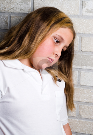 Depression stock photo, A young depressed girl is leaning her head against some bricks by Richard Nelson