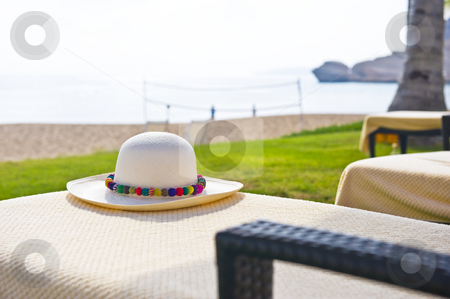 A Panama hat with colorful brim stock photo, A Panama hat on a chair next to the beach with colorful decoration. by Nicolaas Traut