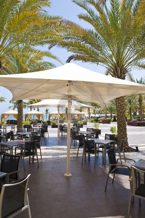 Outside restaurant stock photo, An outside restaurant with nice place settings, situated next to the sea and surrounded by palm trees. by Nicolaas Traut