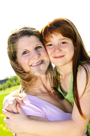 Mother and daughter hugging stock photo, Portrait of happy child hugging her mother by Elena Elisseeva