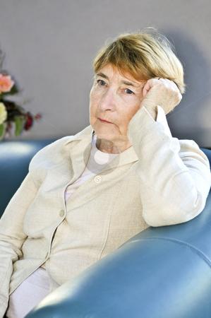 Sad elderly woman stock photo, Sad elderly woman sitting on a couch indoors by Elena Elisseeva