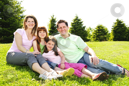 Happy family stock photo, Portrait of happy family of four sitting on grass at the park hugging by Elena Elisseeva