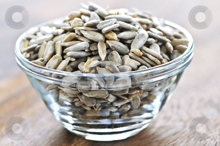 Sunflower seeds stock photo, Shelled sunflower seeds close up in glass bowl by Elena Elisseeva