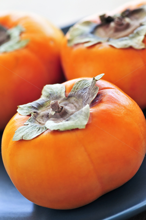 Persimmons stock photo, Orange whole ripe persimmon fruit on a plate by Elena Elisseeva