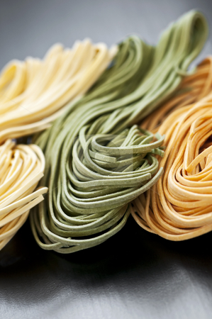 Tagliolini pasta stock photo, Assorted bundles of colorful raw tagliolini pasta noodles by Elena Elisseeva