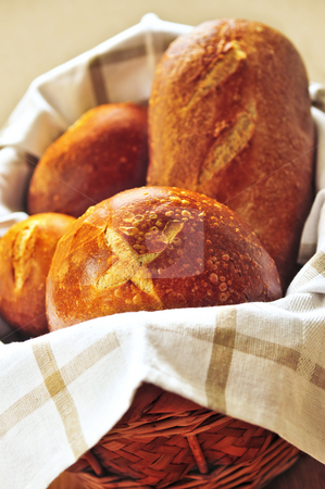 Bread in basket stock photo, Small and large round loaves of sourdough bread in basket by Elena Elisseeva