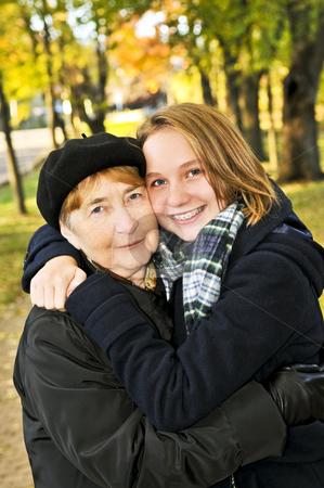 Granddaughter hugging grandmother stock photo, Teen granddaughter hugging grandmother in autumn park by Elena Elisseeva