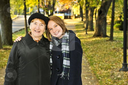 Granddaughter walking with grandmother stock photo, Teen granddaughter walking with grandmother in autumn park by Elena Elisseeva
