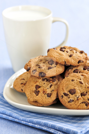 Milk and chocolate chip cookies stock photo, Plate of chocolate chip cookies with milk by Elena Elisseeva