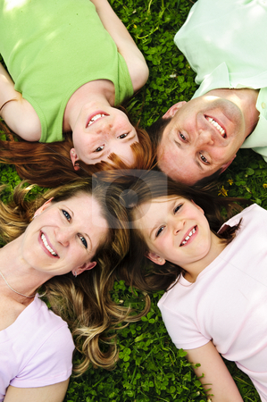 Happy family stock photo, Portrait of happy family laying  on grass looking up heads together by Elena Elisseeva