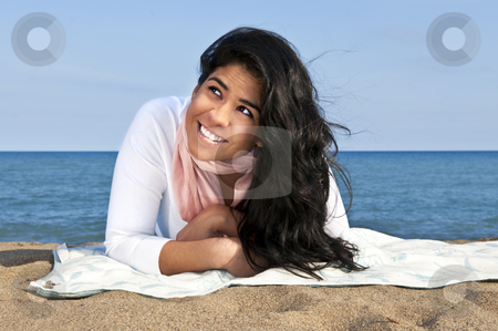 Young native american woman at beach stock photo, Portrait of beautiful smiling native american girl laying at beach looking up by Elena Elisseeva