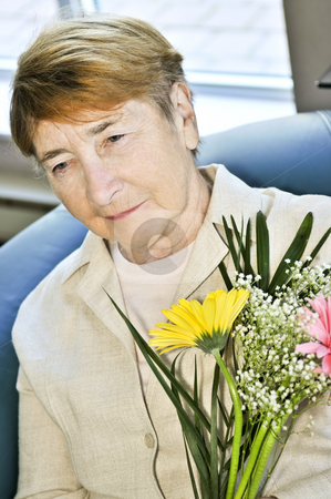 Sad elderly woman with flowers stock photo, Portrait of sad elderly woman holding flowers by Elena Elisseeva
