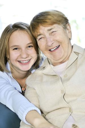 Granddaughter hugging grandmother stock photo, Teen granddaughter hugging grandmother laughing and smiling by Elena Elisseeva