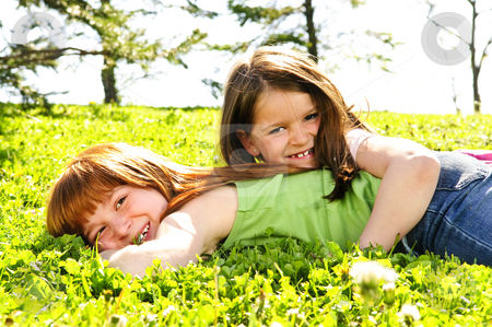 Young sisters stock photo, Portrait of happy girls playing on grass by Elena Elisseeva